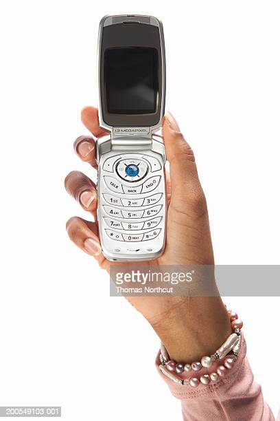 Young woman holding cell phone, close-up of hand