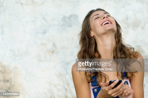 Young woman holding cell phone, laughing : Foto de stock
