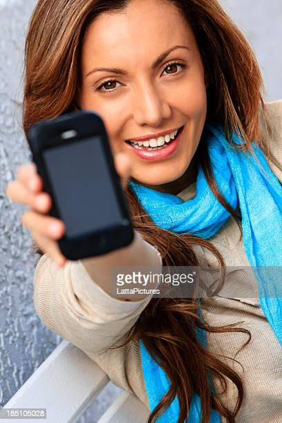 Young woman holding cell phone towards camera face of phone