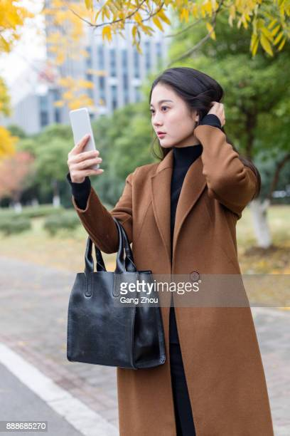 young woman holding cellphone styling her hair
