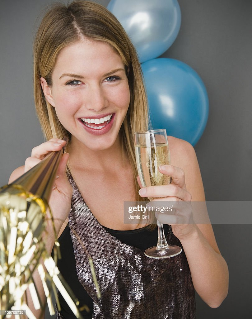 Young woman holding champagne and a noisemaker : Stock Photo
