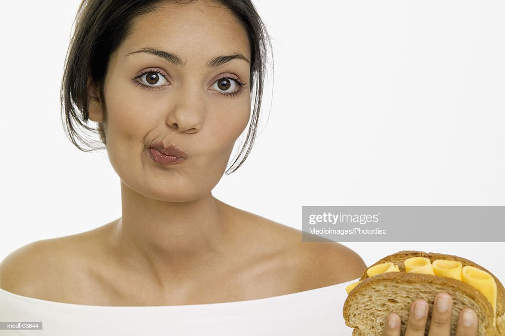 Young woman holding cheese sandwich and making a face, close-up : Stock Photo