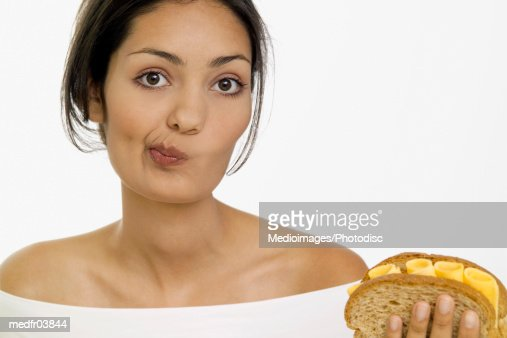 Young woman holding cheese sandwich and making a face, close-up : Stockfoto