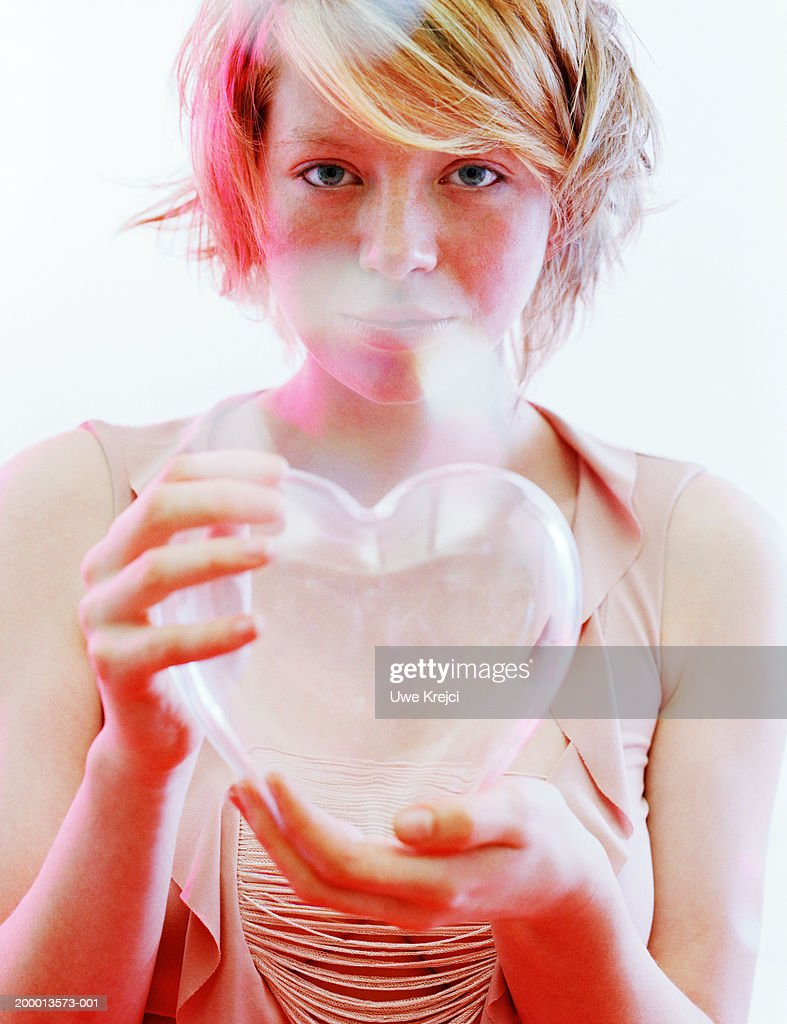 Young woman holding clear heart shaped ornament, portrait : Stock Photo