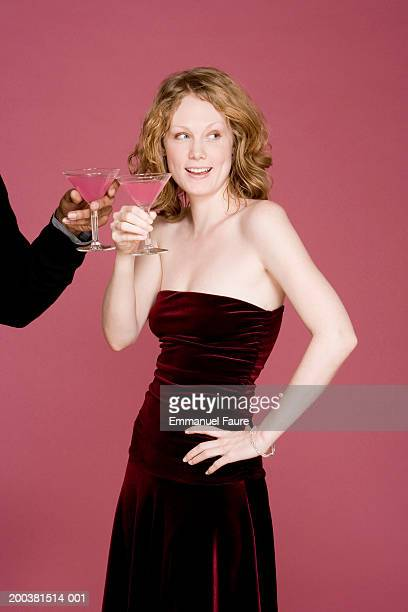Young woman holding cocktail, looking to side