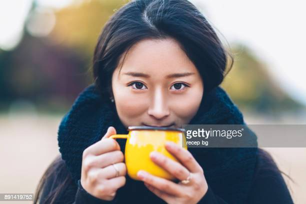 Young Woman Holding Coffee Cup And Looking At Camera