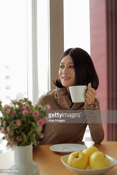 Young woman holding coffee looking out the window
