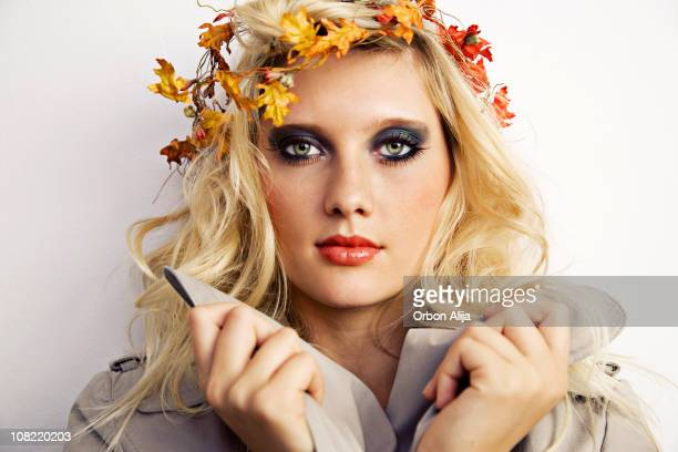 Young Woman Holding Collar Wearing Autumn Leaves in Hair