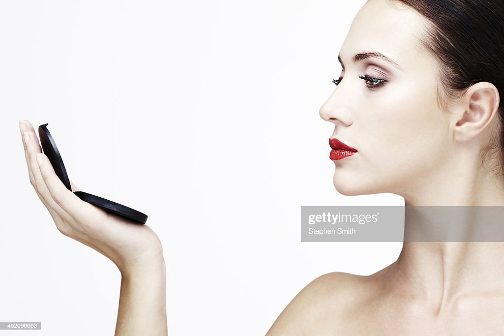 young woman holding compact : Stock Photo