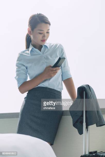 young woman holding cordless phone next by hotel window