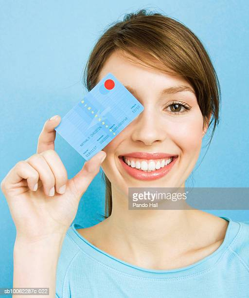 Young woman holding credit card over eye, smiling, portrait, head and shoulders