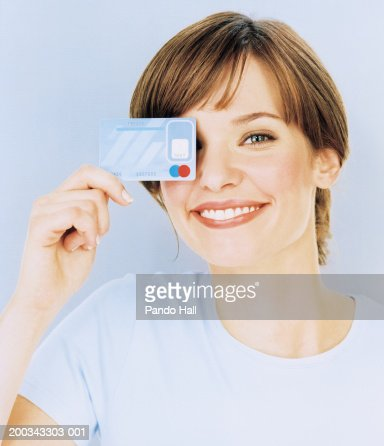 Young woman holding credit card over one eye, smiling, close-up : Stock Photo
