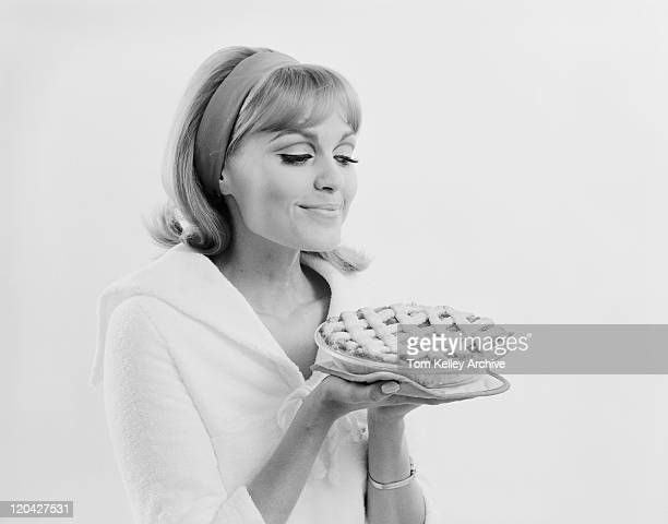 Young woman holding dessert pie against white background, smiling