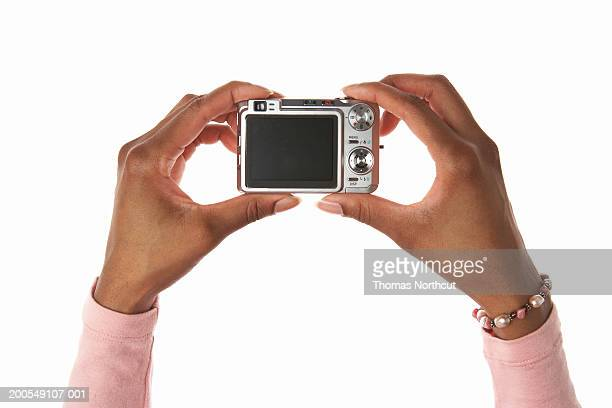 Young woman holding digital camera, close-up of hands