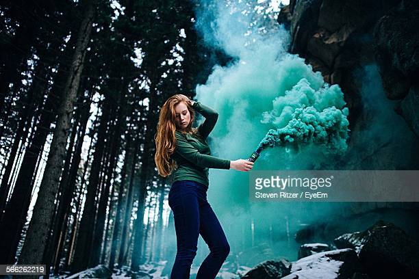 Young Woman Holding Distress Flare In Forest During Winter