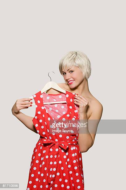 Young woman holding dress