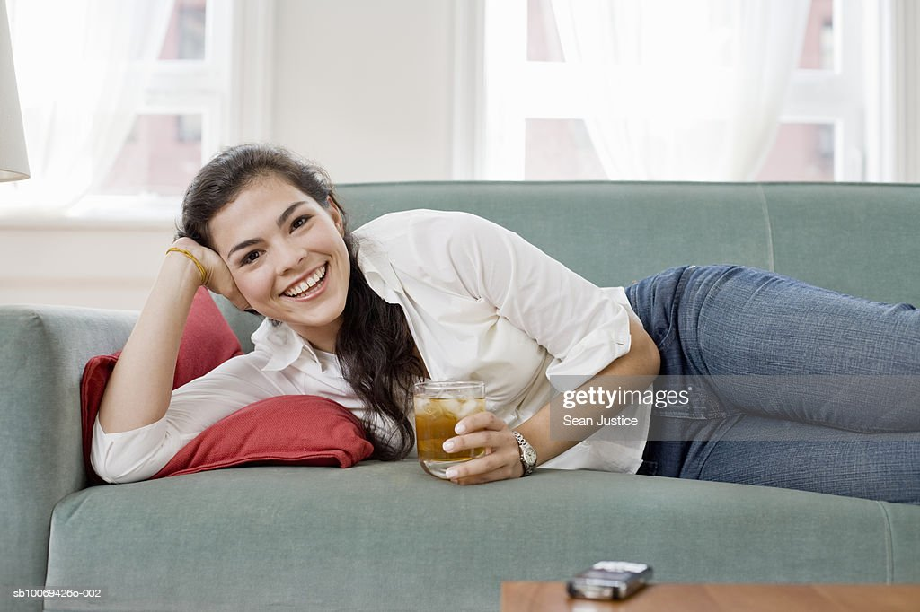 Young woman holding drink lying on sofa, portrait : Stock Photo