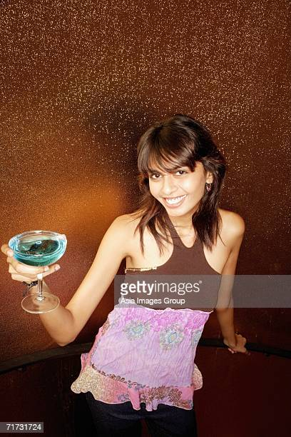 Young woman holding drink, smiling at camera