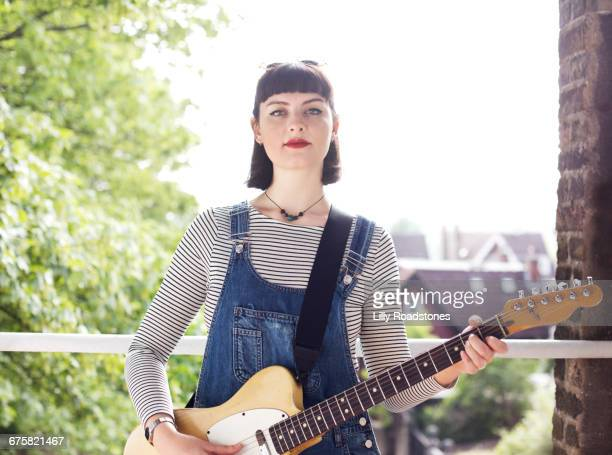 Young woman holding electric guitar