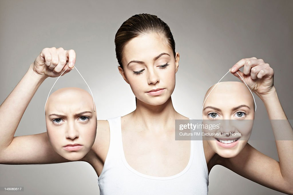 Young woman holding emotive masks : Stock Photo