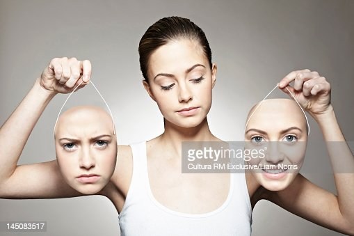 Young woman holding emotive masks  Stock Photo
