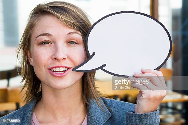 Young woman holding empty speech bubble