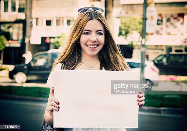 Young woman holding empty white placard
