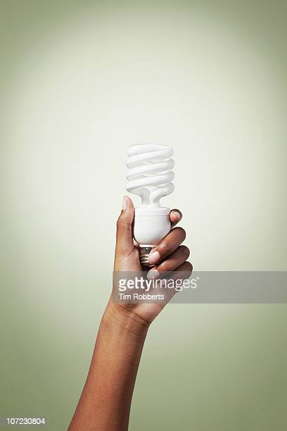 Young woman holding energy efficient light bulb.