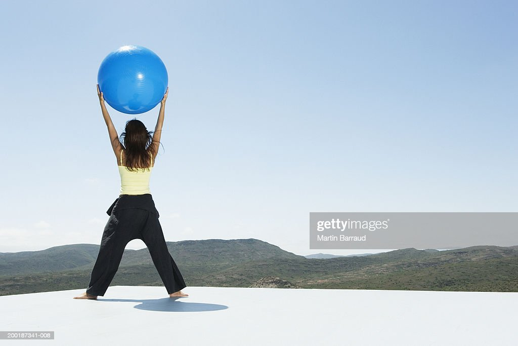 Young woman holding exercise ball above head, outdoors, rear view : Stock Photo