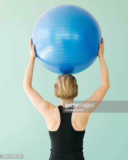 Young woman holding exercise ball above head, rear view