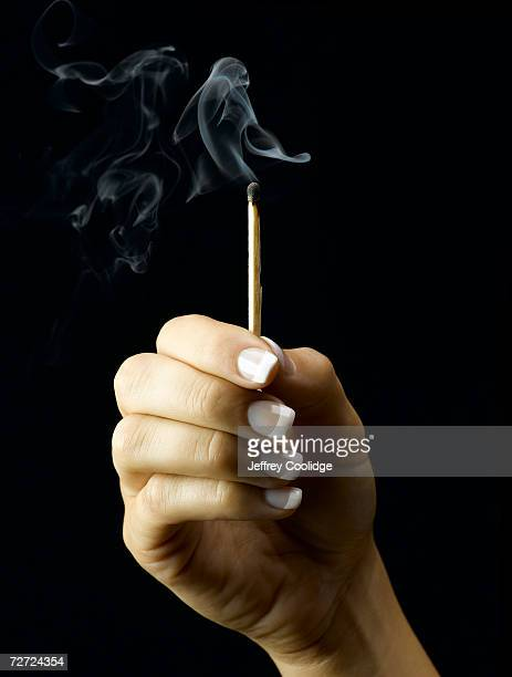 Young woman holding extinguished, smoking match, close-up of hand