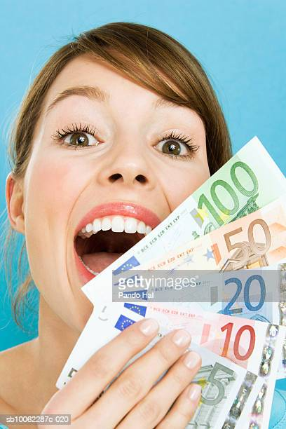 Young woman holding fan of Euro banknotes and laughing, portrait, close-up