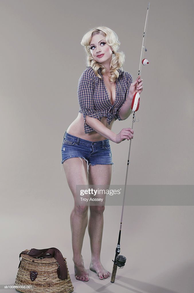 Young woman holding fishing rod : Stock Photo