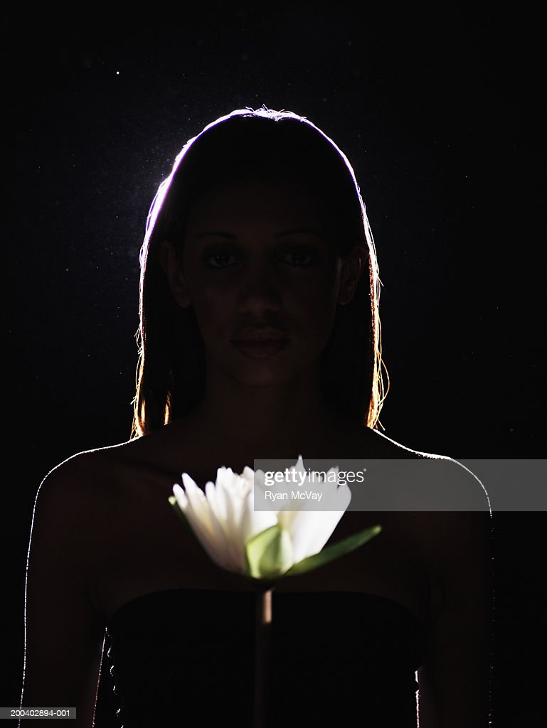 Young woman holding flower, portrait : Stock Photo