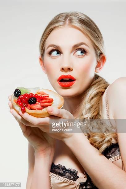 Young woman holding fresh fruit tart