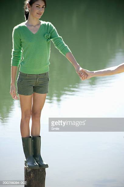 Young woman holding friend's hand in lake, smiling, portrait