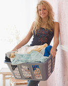 Young woman holding full laundry basket at home, smiling, portrait
