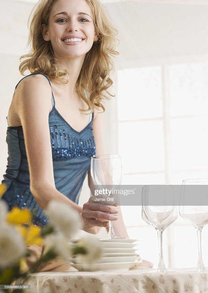 Young woman holding glass at table smiling, portrait : Stock Photo
