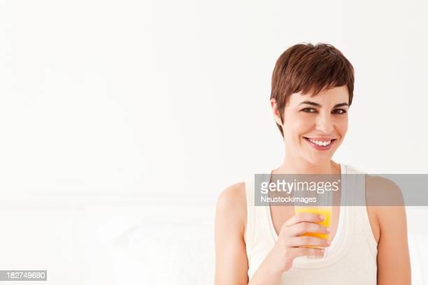 Giovane donna con un bicchiere di succo d'arancia e sorridente