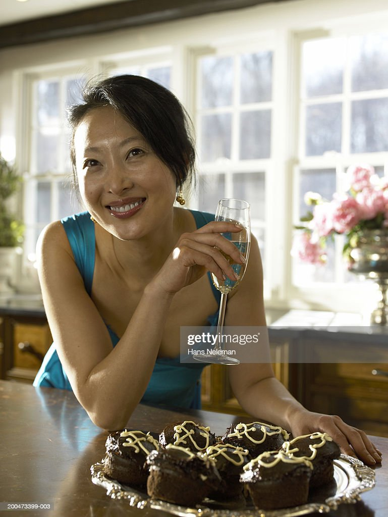 Young woman holding glass of wine, plate of brownies in front : Stock Photo