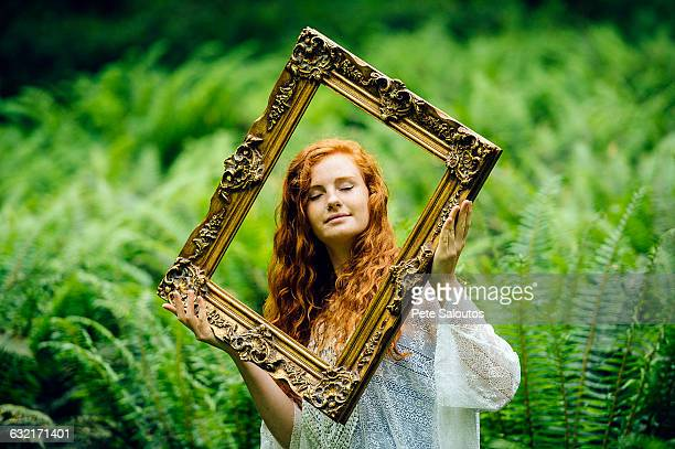 Young woman holding gold picture frame amongst forest ferns