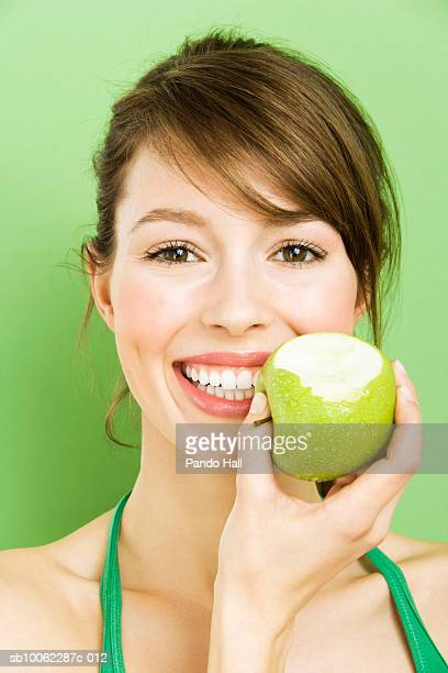 Young woman holding green apple over face, smiling, portrait, head and shoulders