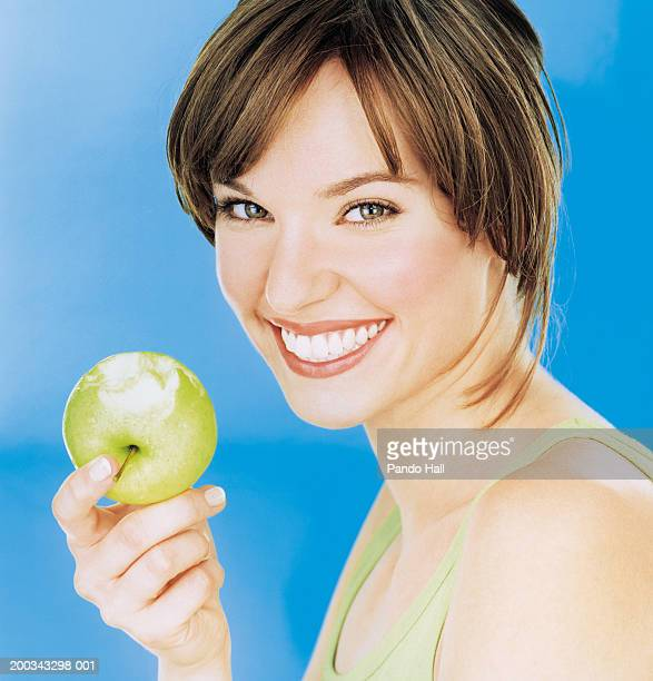 Young woman holding half eaten apple, smiling, portrait, close-up
