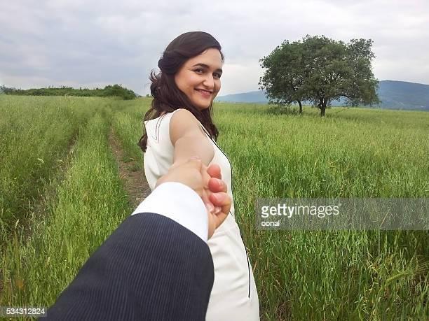 Jeune femme tenant la main de son mari dans un paysage verdoyant