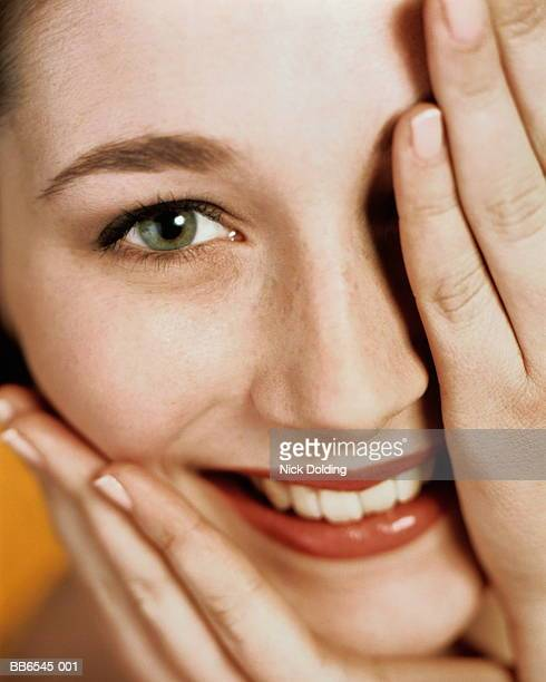 Young woman holding hand over one eye, smiling, close-up