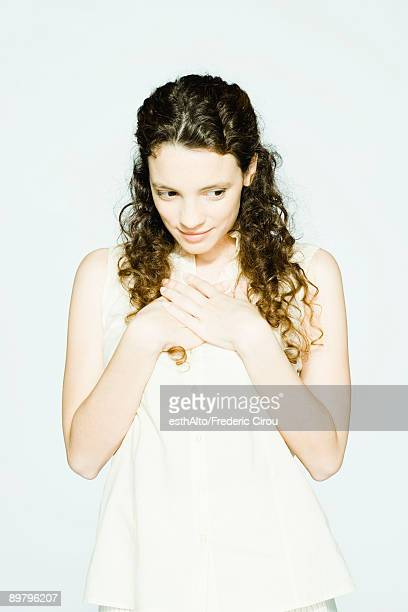 Young woman holding hands over heart, looking away