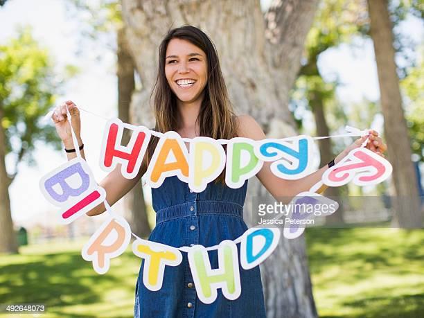 Young woman holding Happy birthday banner Salt Lake City, Utah, USA