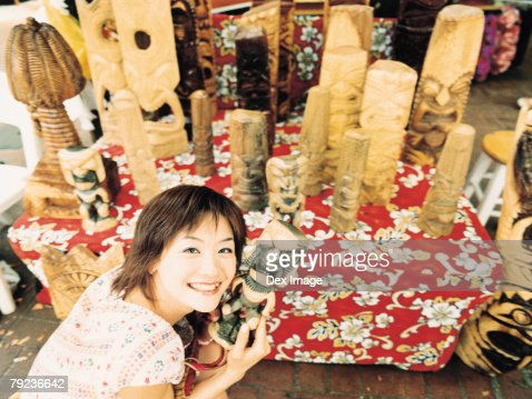 Young woman holding Hawaiian handicraft, smiling : Stock Photo