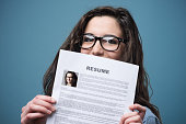Young woman hiding behind her resume