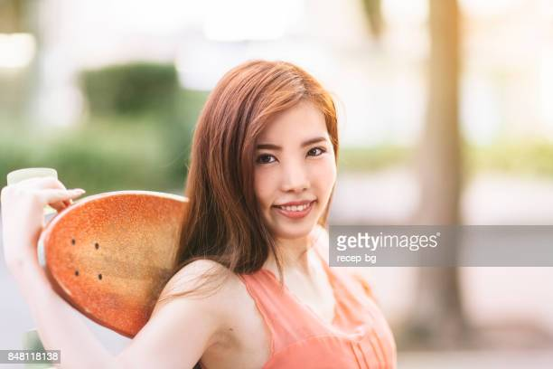 Young Woman Holding Her Skateboard